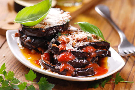 eggplant parmesan decorated with basil leaves