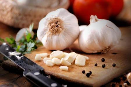 sliced garlic on wooden chopping board Standard-Bild