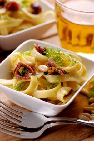 pignons de pin: nouilles avec des anchois, pignons de pin et fenouil dans un bol blanc Banque d'images
