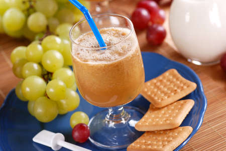 thirst quenching: grape smoothie in the glass beaker with fruits around