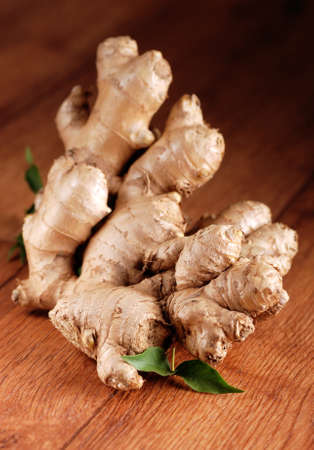 antirheumatic: organic ginger in the foreground on wooden table Stock Photo