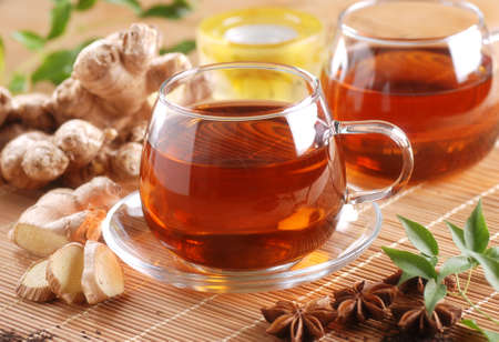 ginger tea in glass cup with ingredients around Standard-Bild