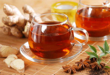 tea hot drink: ginger tea in glass cup with ingredients around Stock Photo