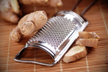 antirheumatic: ginger and grater on wooden table