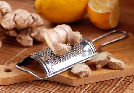 antirheumatic: ginger and grater on wooden chopping board