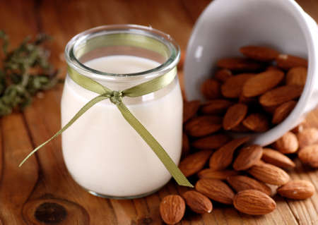 glass of milk: almond milk in glass jar with fruits around