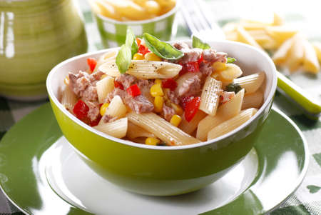 salads: pasta salad with tuna and corn in green bowl Stock Photo