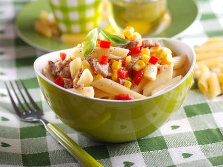 salad fork: pasta salad with tuna and corn in green bowl Stock Photo