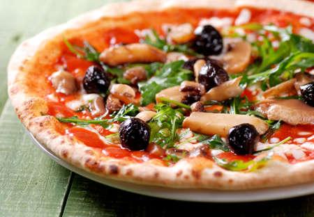 Italian pizza with arugula and mushrooms on green table