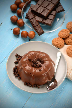 custard flavor: chocolate pudding with ingredients around on the table blue Stock Photo