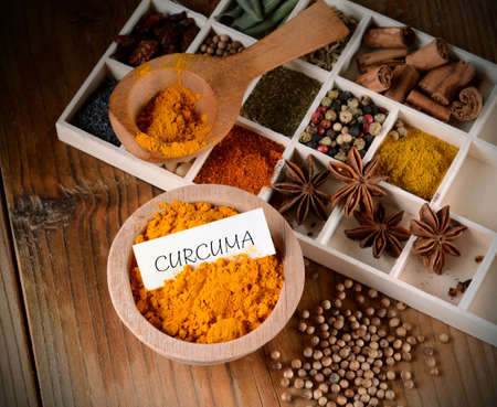 blend: turmeric powder in wooden bowl with other spices around