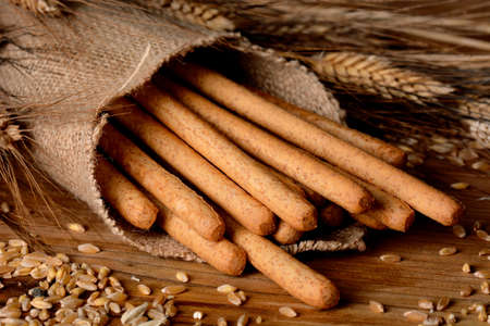 breadstick: Crispy bread sticks on the table with ears of wheat around