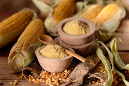 corn flour in wooden bowl with the cobs around