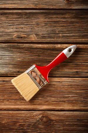 redecorate: paintbrush with red handle on the wooden table Stock Photo