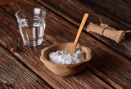 agua con gas: bicarbonato de sodio en el recipiente con una cuchara de madera