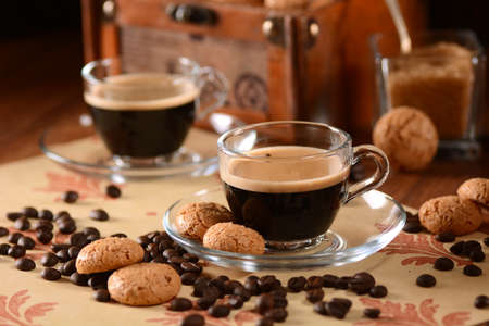 coffee mugs: Italian espresso coffee in glass cup with amaretti biscuits around