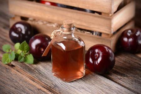 ciruela pasa: jugo de ciruela en la peque�a botella de cristal con frutas alrededor Foto de archivo