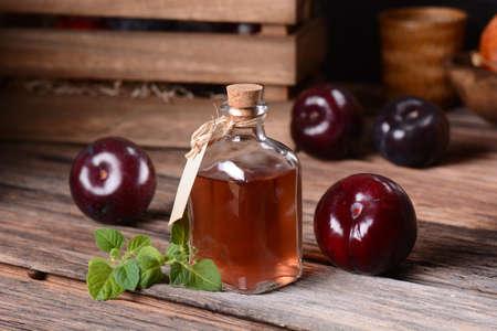 podar: jugo de ciruela en la pequeña botella de cristal con frutas alrededor Foto de archivo
