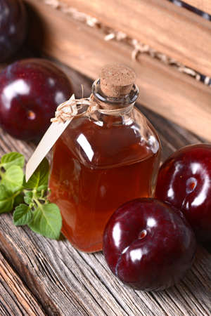 prune: prune juice in small glass bottle with fruit around Stock Photo