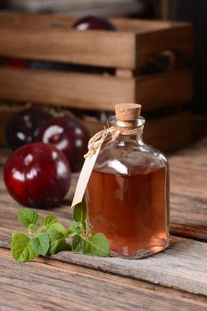 ciruela pasa: jugo de ciruela en la pequeña botella de cristal con frutas alrededor Foto de archivo