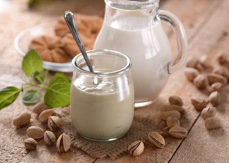 pistachio yogurt in glass jar with fruit around Stock Photo
