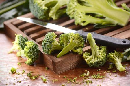 chopping board: green raw broccoli on wooden chopping board Stock Photo