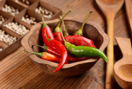 kilos: red chili, green and orange in wooden bowl