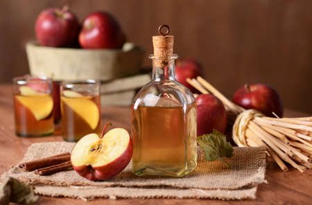 apple cider in glass bottle with fruit around Stock Photo