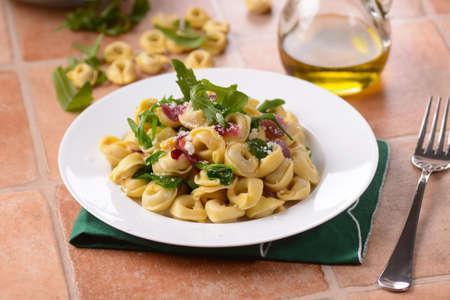 cebolla roja: tortellini italianos con r�cula y cebolla roja Foto de archivo