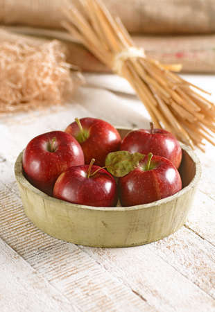 organic red apples in wooden bowl Stock Photo