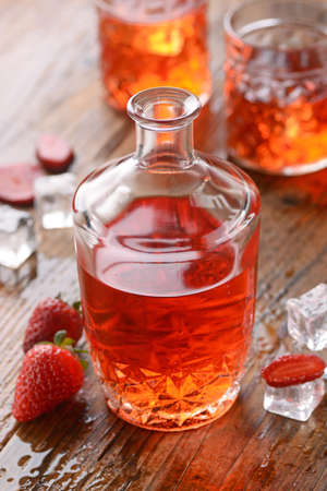 liqueurs: strawberry liqueur on the table with fruit around
