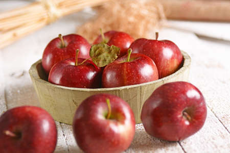 clic: organic red apples in wooden bowl Stock Photo