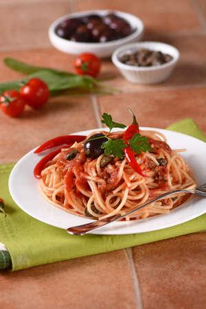 puttanesca: Spaghetti puttanesca - Traditional Italian recipe with anchovies, capers, tomato and chilli Stock Photo