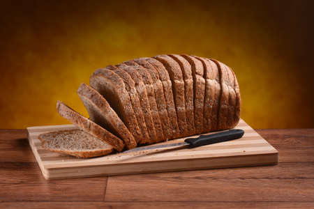 sliced bread loaf on wooden cutting board Imagens