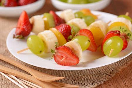 brochetas de frutas: brochetas de frutas surtidos con las uvas, kiwi, plátano, fresa y ciruela Foto de archivo