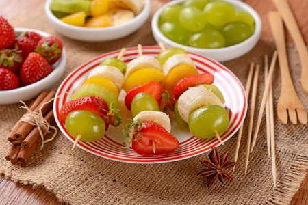 brochetas de frutas: brochetas de frutas surtidos con las uvas, kiwi, pl�tano, fresa y ciruela Foto de archivo