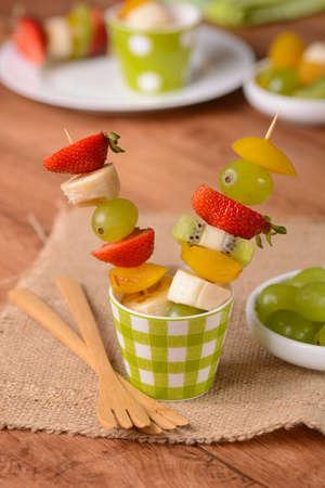 brochetas de frutas: assorted fruit skewers with grapes, kiwi, banana, strawberry and plum Foto de archivo