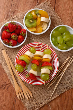 fruit skewers: assorted fruit skewers with grapes, kiwi, banana, strawberry and plum Foto de archivo
