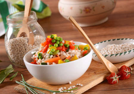 Barley salad and assorted vegetables in white bowl Stock Photo