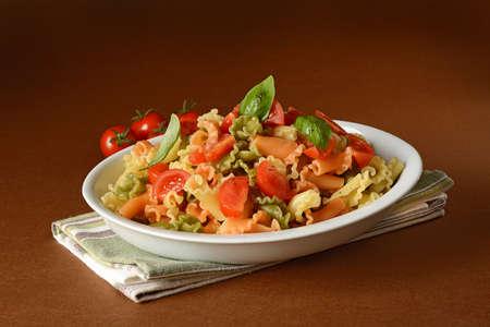 macarrones: Colorful pasta with cherry tomato and basil - closeup Foto de archivo