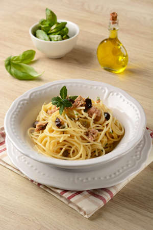 Spaghetti with tuna, capers and black olives - closeup