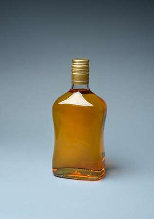 bottle of whiskey on gray background - isolated - closeup