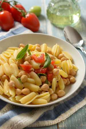 Italian gnocchi pasta with tomatoes, basil and chickpeas - closeup Standard-Bild