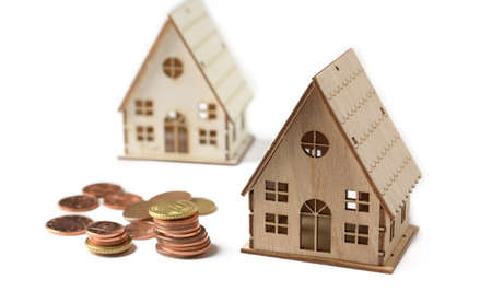 little house model on a white background with coins beside - closeup