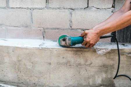 cutter: Builder worker with grinder machine cutting finishing concrete wall at construction site