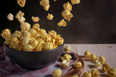 Caramel covered popcorn in black ceramic bowl on wooden table,  levitation popcorn and mystic photography