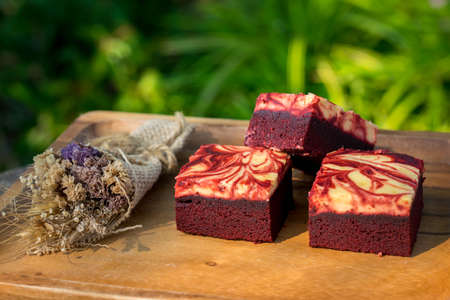 Red velvet cream cheese brownies on wooden plate Archivio Fotografico