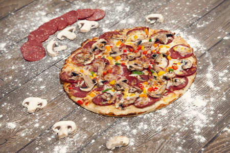 roquette: Freshly baked pizza topped with salami and mushrooms on a wooden table Stock Photo