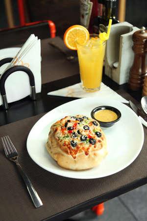 Piccola pizza / pizzetto con formaggio, olive e salsa su un tavolo in un ristorante Archivio Fotografico - 80932446