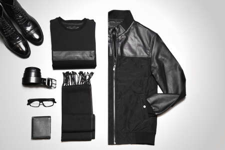 Flat lay of men's casual outfits with accessories including sweater, jacket, scarf, glasses, belt, wallet and shoes in black colors.